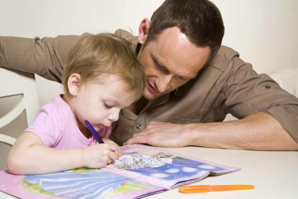 Father helping young daughter with book