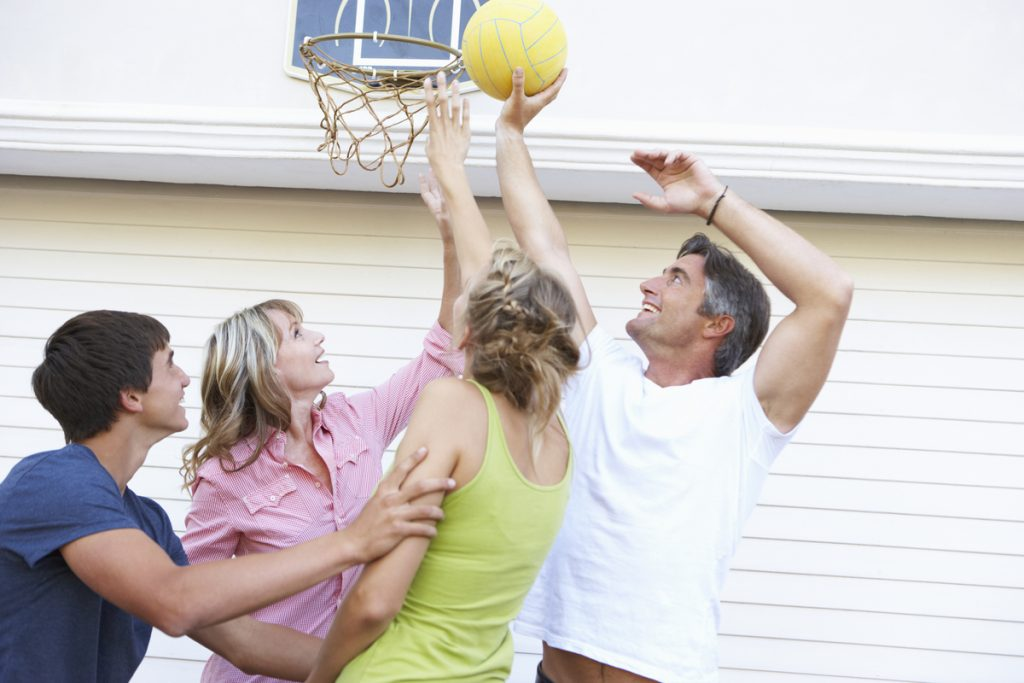 Teenage Family Playing Basketball Outside Garage